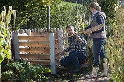 Man and Woman building compost containers together
