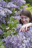 Woman cutting lilac in spring garden