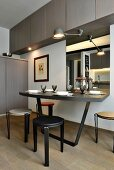 Minimalist dining area below wall-mounted cupboards