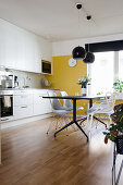 Modern dining table in kitchen-dining room with yellow wall
