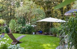 Wooden lounger on lawn and parasol in well-tended garden
