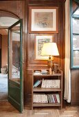 Table lamp on bookshelves against wood-panelled wall in hallway