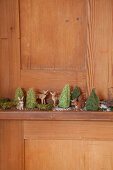 Miniature forest of animal figurines and tiny crocheted trees