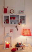 Red and white ornaments on wall-mounted cabinet and desk