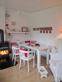 Lit candles in log burner next to table in white dining room