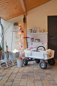 Pull-along cart and Christmas decorations under porch