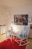 Rocking chair and side table on red rug in front of photo