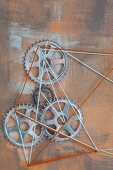 String art with cogs on rust-coloured background
