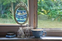 Earrings hung from crocheted trim in oval picture frame in front of window