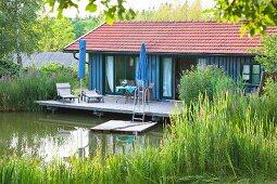Haus am See mit Terrasse über dem Wasser und Badeplattform