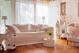 Scatter cushions on white loose-covered sofa in shabby-chic interior