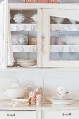 Crockery in shabby-chic dresser with glass-fronted upper section and open glass door