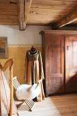 Historical clothing on tailors' dummy next to antique wooden wardrobe, sheepskin on chair and harp