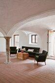 White cross-vaults, pillars and green sofa set on brick floor