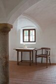 White cross-vault, pillar, brick floor and armchair next to wooden table