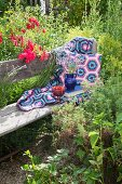 Crocheted blanket and cushions on wooden bench in cottage garden