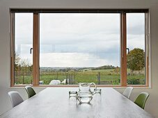 View of landscape through large window across dining table