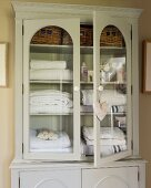 Towels in glass-fronted linen cupboard