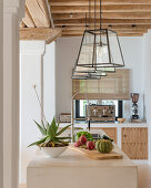 Lanterns above island counter in Mediterranean kitchen