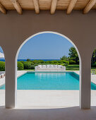 View of pool and long outdoor sofa seen through archades