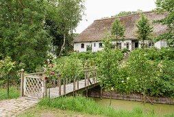 Traditional Frisian 17th-century farmhouse with wooden bridge over stream