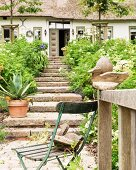 Vintage garden chair, wooden duck and stone steps outside Frisian famhouse