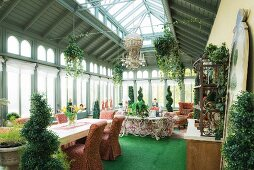 Green carpets and box hedge topiary in orangery with dining area and floral sofa
