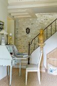 Antique bureau at foot of staircase with stone wall in traditional country house