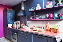 Dark kitchen counter with pink worksurface below hot pink shelves