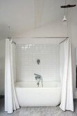 White bathtub with shower curtain in renovated period building