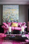 Pinkfarbene Couch mit Kissen und schwarzer Couchtisch vor Gemälde mit moderner Malerei