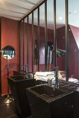 Black sinks against glass partition wall of ensuite bathroom