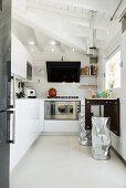 Weiße Einbauküche mit hellem Boden und Frühstückstisch