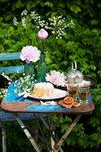 Gartentisch mit Pfingstrosen, Gugelhupf und Frühlingskräutertee