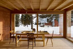 Dining room in modern wooden house with view of wintry landscape