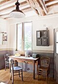 Rustic kitchen table, wooden chairs and vintage post boxes hung on wall