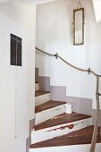 Restored wooden staircase with rope handrail