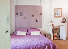 Double bed with purple bed linen, colour coordinated panel on wall and disused fireplace