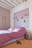 Double bed with purple bed linen and colour coordinated panel on wall