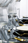 Elegant place setting with wine glass on black glossy table