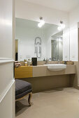 Bathroom with long washstand and mirrored wall