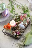 Easter arrangement in decorative wire basket on wooden table