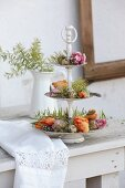 Parrot tulips, touch-me-not, quail eggs and feathers on vintage cake stand
