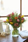 Luxuriant bouquet of tulips and delicate touch-me-not in glass vase next to china rabbits