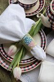 Linen napkin with embroidered napkin ring and tulips on plate