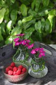 Posies of pinks in oil carafes decorated with plaited grasses next to little bowl of raspberries