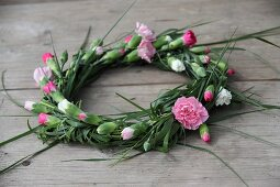 Wreath of carnations on wooden surface