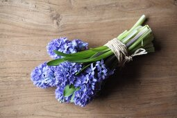 Bouquet of hyacinths tied with raffia on wooden table