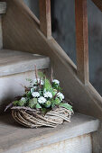 Wreath decorated with white asters and poppy seedheads on wooden staircase