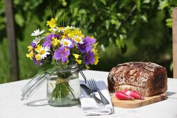 Posy in preserving jar and loaf of bread on table